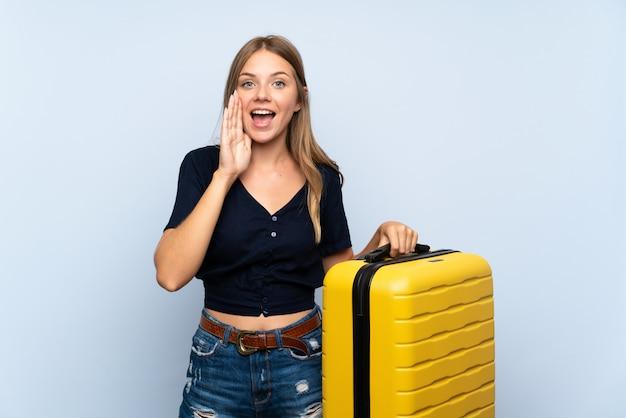 Reiziger blondevrouw die met koffer met wijd open mond schreeuwen