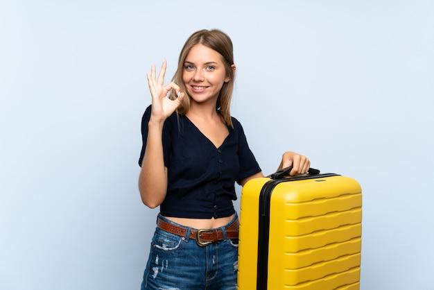 Reiziger blondevrouw met koffer die ok teken met vingers tonen