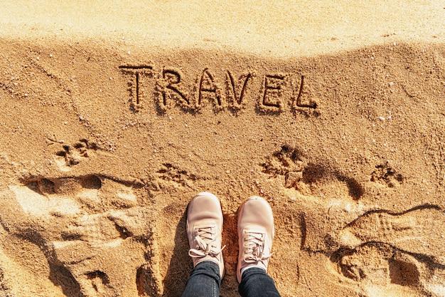 Reiziger bovenaanzicht op zand met tekst reizen. avonturen concept. zomer of woestijn