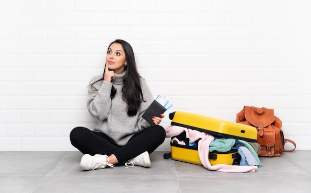 Reiziger colombiaans meisje met een koffer vol kleren die op de vloer zitten die een idee denken