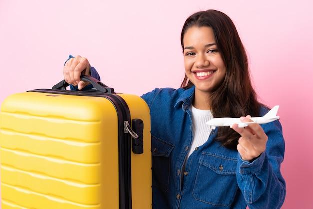 Reiziger colombiaanse vrouw die een koffer over geïsoleerde roze muur houdt