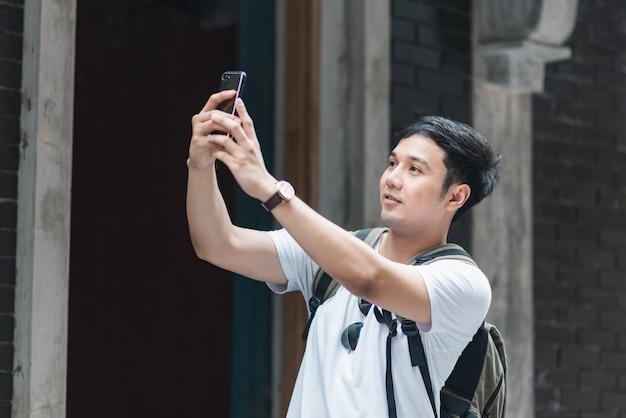 Reiziger de aziatische mens die mobiele telefoon met behulp van voor neemt een beeld terwijl het besteden vakantiereis in peking, china