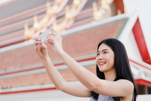 Reiziger de aziatische vrouw die mobiele telefoon met behulp van voor neemt een beeld terwijl het besteden vakantiereis in bangkok, thailand