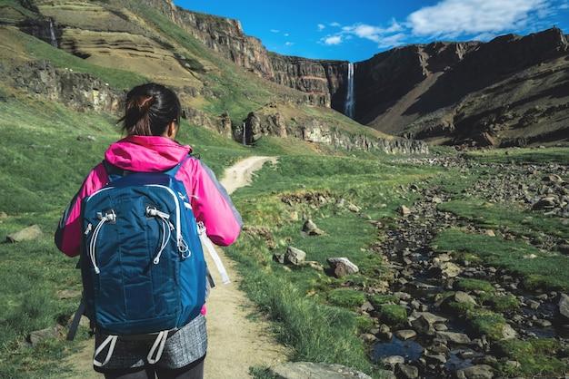 Reiziger die bij hengifoss-waterval, ijsland wandelen.