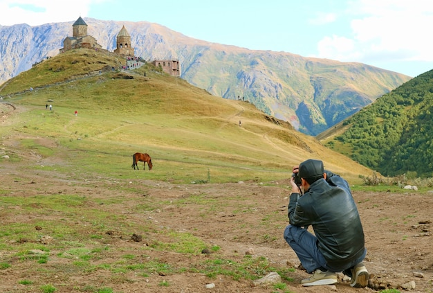 Reiziger die de drievuldigheidskerk van gergeti in stepantsminda-stad, kazbegi, georgië fotografeert