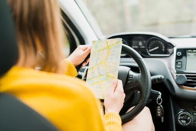 Reiziger die de kaart in auto controleert