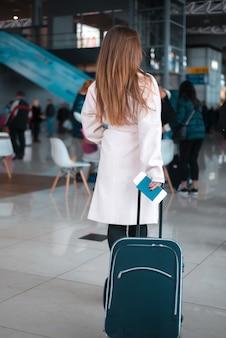 Reiziger die door de luchthavenhal loopt.