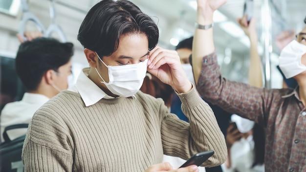 Reiziger die een gezichtsmasker draagt tijdens het gebruik van een mobiele telefoon in de openbare trein