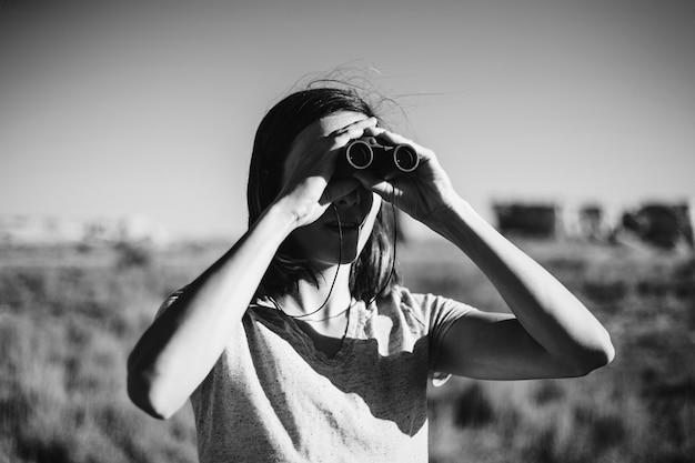 Reiziger die een verrekijker gebruikt om een vogel te spotten