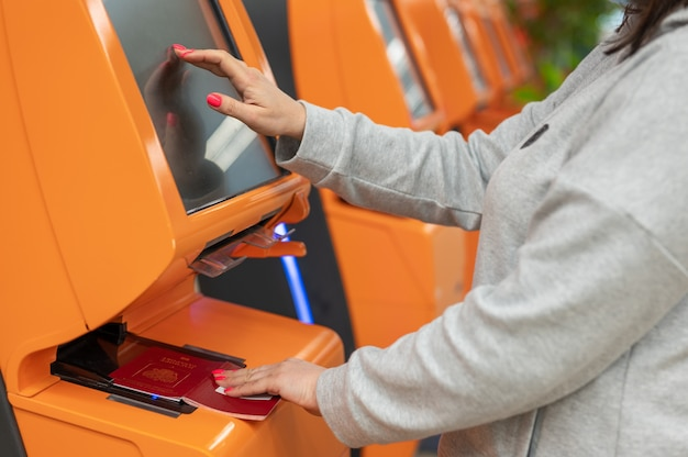 Reiziger die een zelf-incheckmachine-kioskservice gebruikt op de luchthaven, close-up van de vinger op het display, technologie en slimme applicatie om vluchtboekingsdetails te bevestigen, reisconcept.