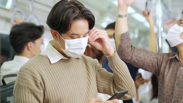 Reiziger die gezichtsmasker draagt tijdens het gebruik van mobiel
