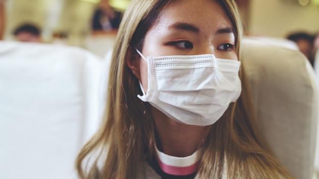 Reiziger die gezichtsmasker draagt tijdens het reizen in een commercieel vliegtuig