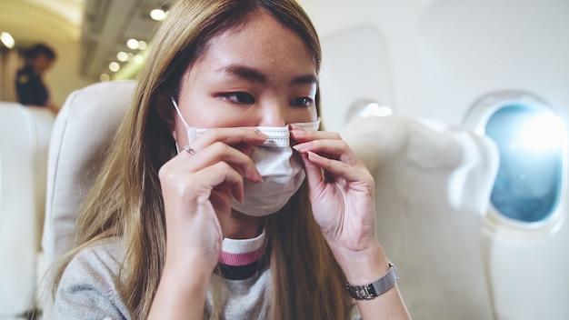 Reiziger die gezichtsmasker draagt tijdens het reizen met een commercieel vliegtuig.
