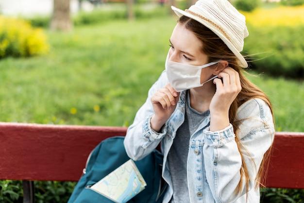 Reiziger die haar medisch masker schikt