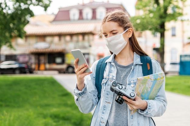 Reiziger die medisch masker draagt dat haar mobiele telefoon met behulp van
