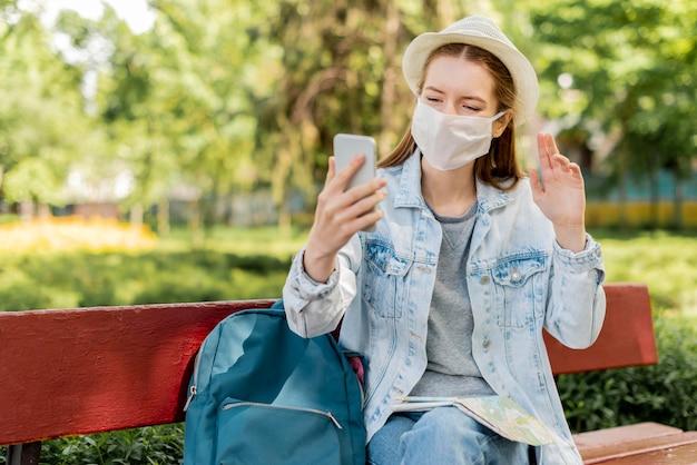 Reiziger die medisch masker draagt dat haar telefoon i gebruikt