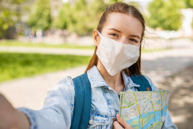 Reiziger die medisch masker en kaart selfie draagt