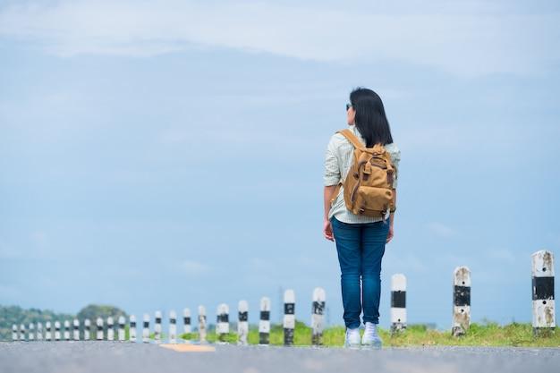 Reiziger die met rugzak blauwe hemel, de vrouw van azië backpacker bekijken die zich op weg bevinden