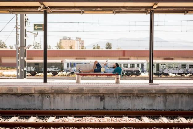 Reiziger die op de bank ligt die op trein wacht