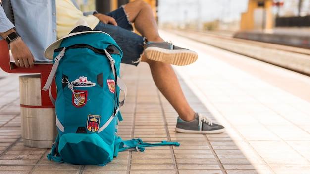 Reiziger die op trein op een bank wacht