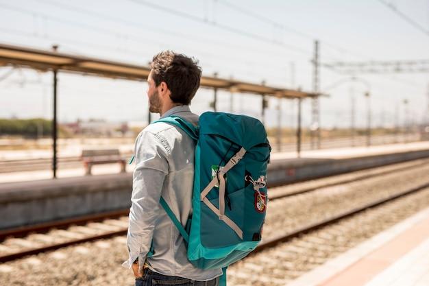 Reiziger die op trein op postplatform wachten