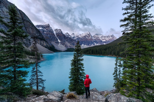 Reiziger die zich op rots met canadese rotsachtige bergen in ochtend bij morenemeer bevinden