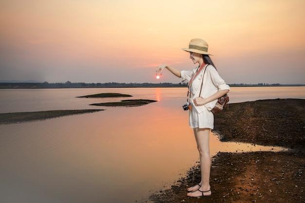 Reiziger draag casual kleding ontspannen bij zonsondergang op rustig meer