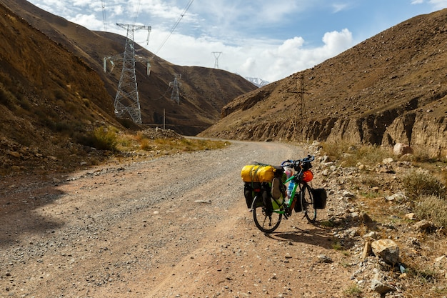 Reiziger fiets met tassen staan op de bergweg, kokemeren rivier, kirgizië, toeristische fiets