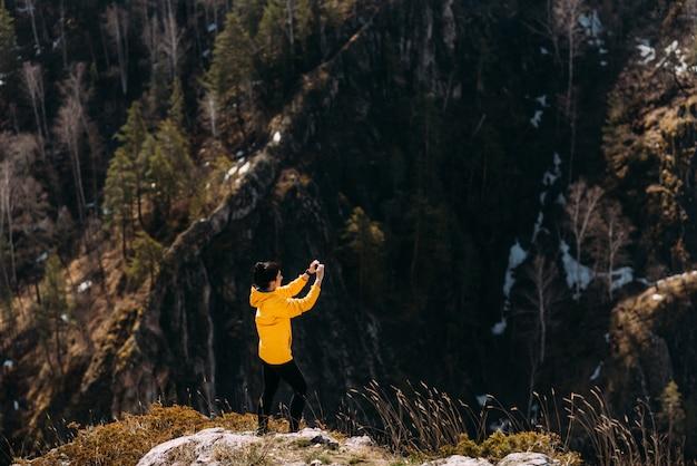 Reiziger fotografeert de natuur in de bergen aan de telefoon. reisfotograaf. maak foto's op uw telefoon. maak foto's op uw smartphone.