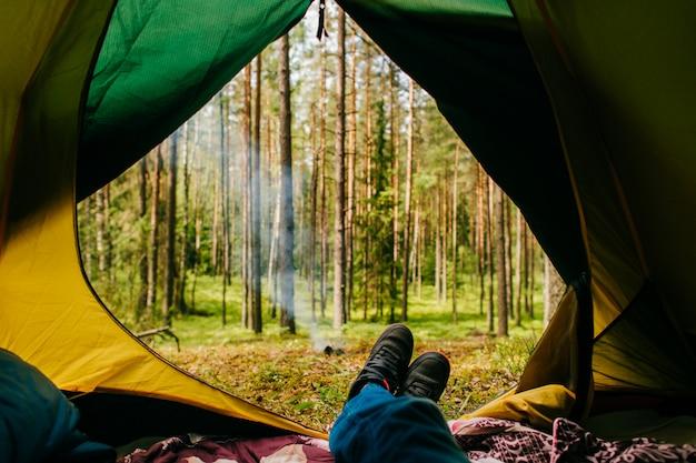 Reiziger geniet van uitzicht op de natuur vanuit zijn camping tent.