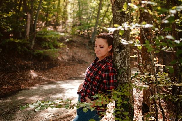 Reiziger hipster vrouw staan in herfst bos in geruit overhemd en spijkerbroek. koud weer, herfstkleuren