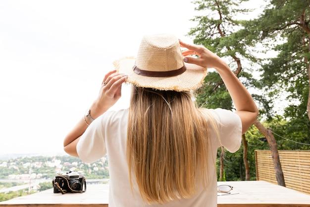 Reiziger houdt haar hoed van achteren vast