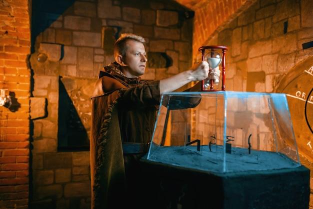 Reiziger houdt zandloper vast en lost een oude puzzel op in de tempelkerk. oude geheimen, fantasielabyrint. man bij het model van de glazen grot