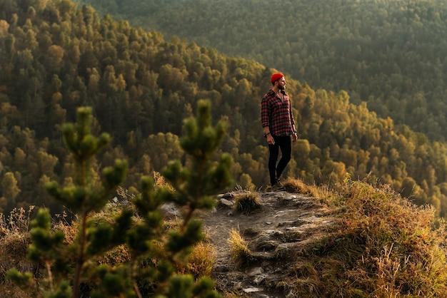 Reiziger in de bergen. een man geniet van een prachtig uitzicht op de bergen. man bij zonsopgang in de bergen. een man reist door de kaukasus. wandelaar bij zonsondergang in de bergen. ruimte kopiëren.