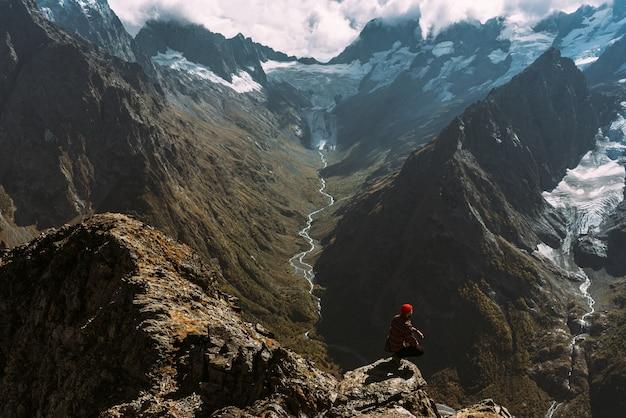 Reiziger in de bergen. een man geniet van een prachtig uitzicht op de bergen. man op de achtergrond van bergen. man bij zonsopgang in de bergen. een man reist door de kaukasus. ruimte kopiëren