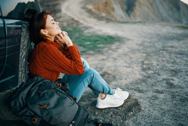 Reiziger in de bergen in de buurt van de auto die in de natuur rust met een rugzak