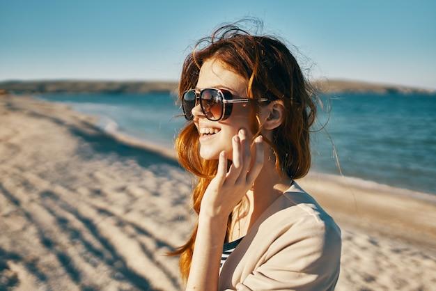 Reiziger in een beige jas en zonnebril op het zand bij de zee op het strand