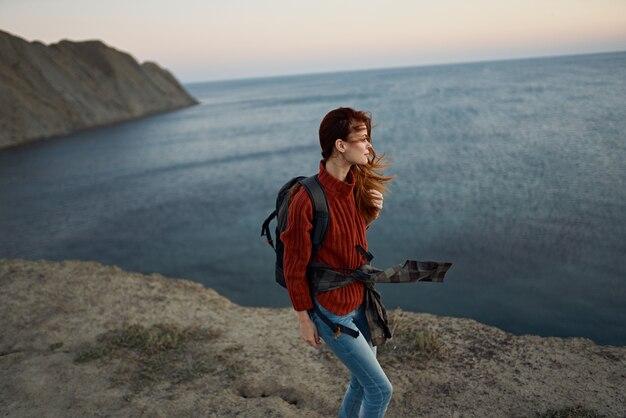 Reiziger in een rode trui en jeans met een rugzak in de bergen bij het bovenaanzicht van de zee