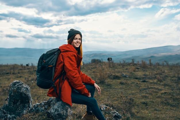 Reiziger in een rood jasje hoeden met een rugzak zit op een steen in de bergen in de natuur