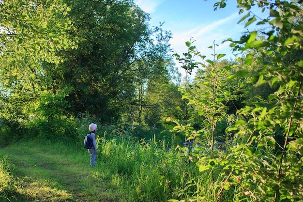 Reiziger jong meisje met rugzak lopen op pad in het tropische woud