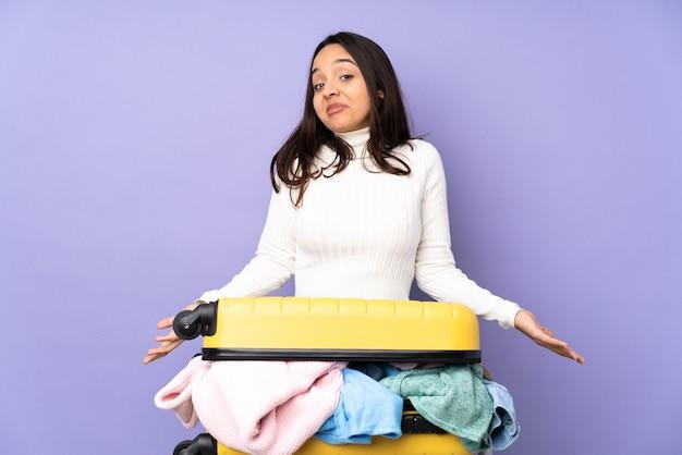 Reiziger jonge vrouw met een koffer vol kleren over geïsoleerde paarse muur glimlachen