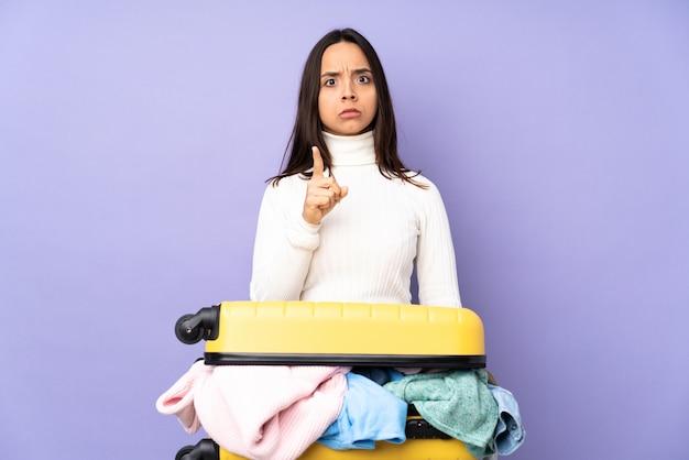 Reiziger jonge vrouw met een koffer vol kleren over paarse muur gefrustreerd en wijzend naar de voorkant