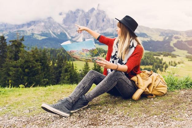 Reiziger jonge vrouw met rugzak en hoed zittend op het gras en de juiste richting op de kaart zoeken