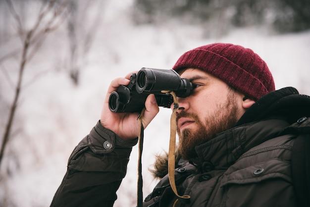 Reiziger kijkt door een verrekijker in de winter