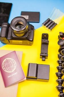 Reiziger kit van camera met verschillende accessoires naast een paspoort op twee gekleurde achtergrond