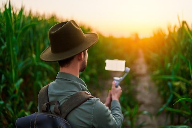 Reiziger man backpacker blogger met elektronische handmatige telefoon stabilisator gimbal met wit leeg scherm mockup neemt een selfie en schiet video blog buitenshuis