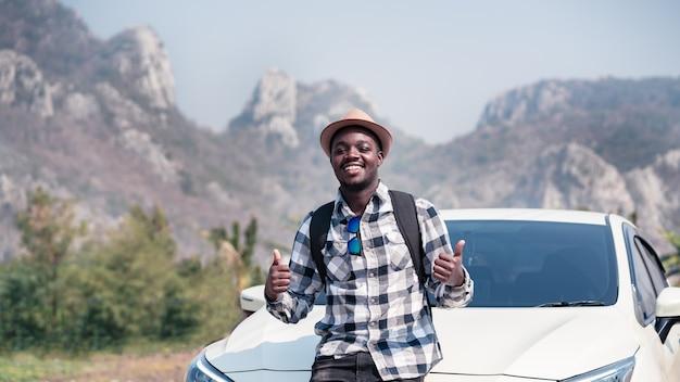 Reiziger man die met auto op de bergen staat. 16: 9 stijl