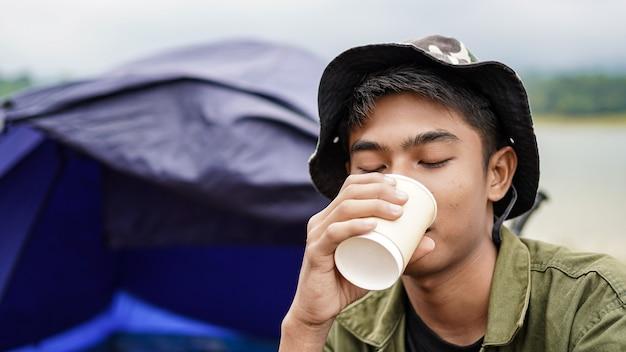 Reiziger man drinkt koffie in het kamp