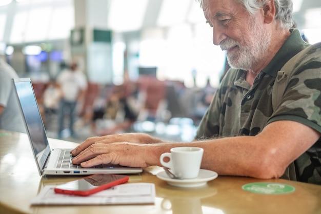Reiziger man in luchthaven wachten op instappen werkt op laptopcomputer, senior blogger werken op afstand, een koffiekopje en mobiele telefoon op tafel