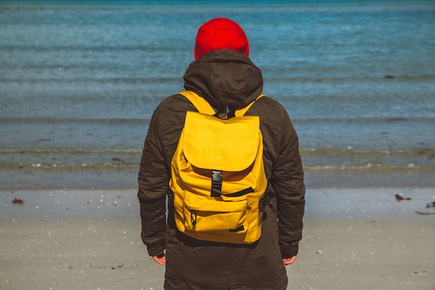 Reiziger man met een gele rugzak staande op een zandstrand op de achtergrond van de zee